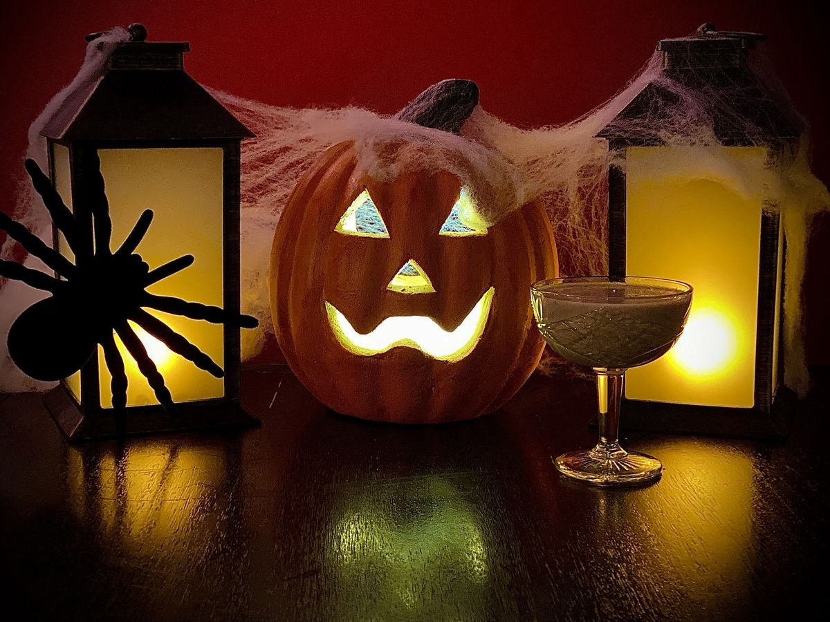 A pumpkin with a giant spide on the left and a drink on the right.