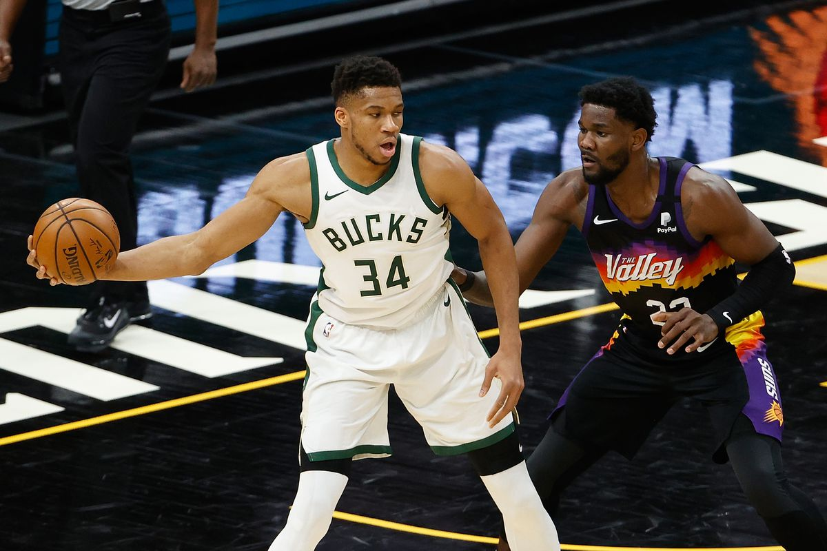 Giannis Antetokounmpo #34 of the Milwaukee Bucks handles the ball against Deandre Ayton #22 of the Phoenix Suns during the first half of the NBA game at Phoenix Suns Arena on February 10, 2021 in Phoenix, Arizona.