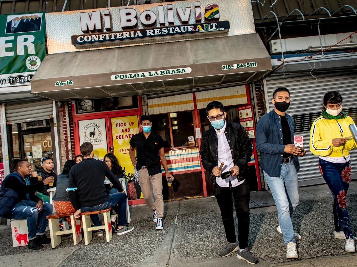 A crowd of diners sits at a large table at Bolivian Llama Party; the old Mi Bolivia sign hangs above the storefront