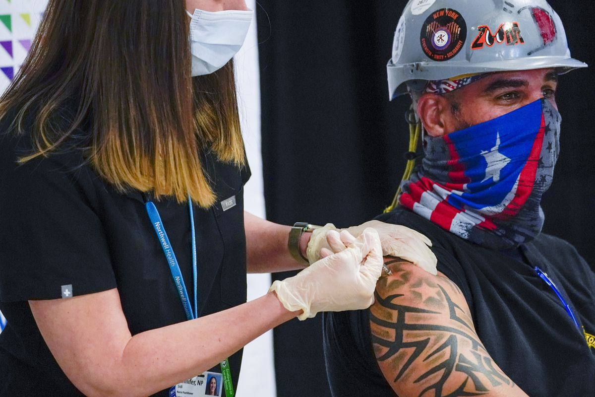 In this April 14, 2021, file photo, Northwell Health nurse inoculates Local 28 Sheet Metal Worker Demetrius Buttelman with the first dose of the Pfizer vaccine during a news conference at the Belmont Park in Elmont, N.Y.