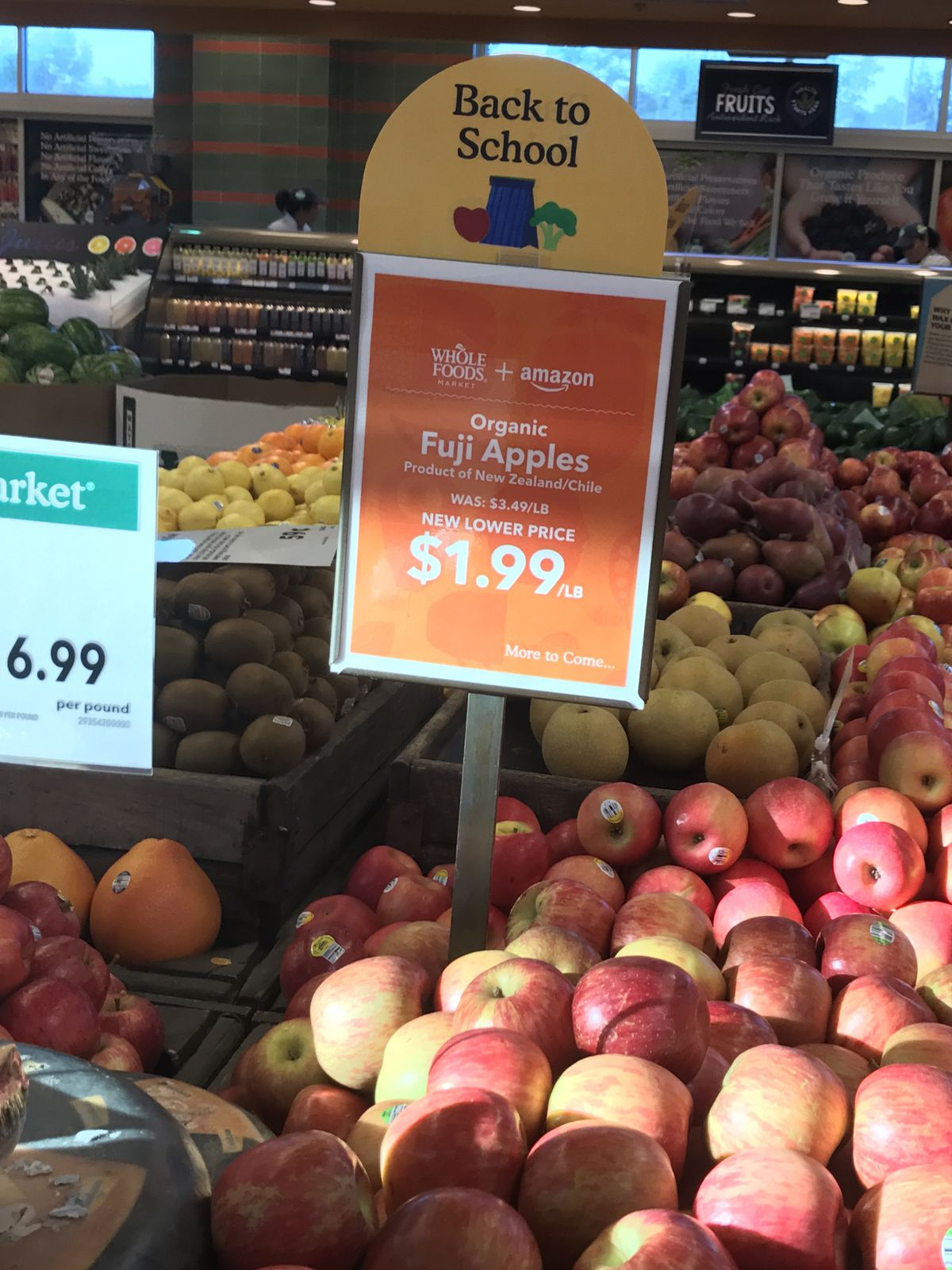 A discount sign for apples inside Whole Foods stores on the first day of Amazon ownership.