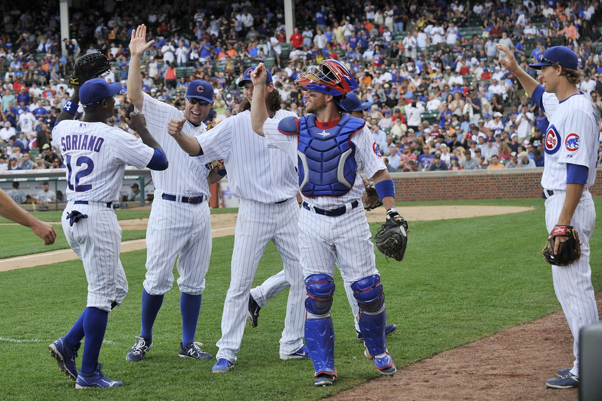 Alfonso Soriano of the Chicago Cubs is congratulated by his teammates after making a diving catch against the San Diego Padres at Wrigley Field in Chicago, Illinois.  (Photo by David Banks/Getty Images)