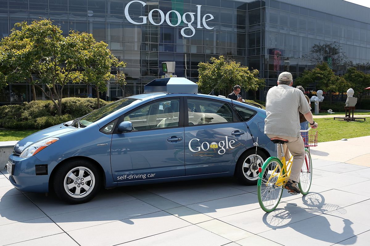 A bicyclist rides by a Google self-driving car at the Google headquartersin Mountain View, California.