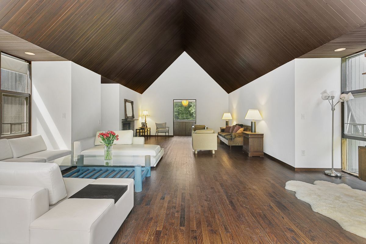 A living room has dark ceilings and wood floors with white walls and an open floor plan.