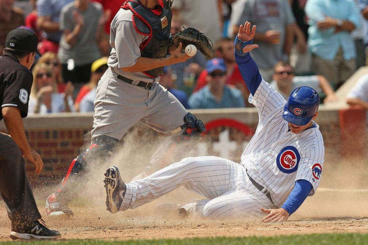 CHICAGO, IL - JULY 27:  Anthony Rizzo #44 of the Chicago Cubs slides safely into home plate as Yadier Molina #4 of the St. Louis Cardinals drops the ball at Wrigley Field on July 27, 2012 in Chicago, Illinois.  (Photo by Jonathan Daniel/Getty Images)