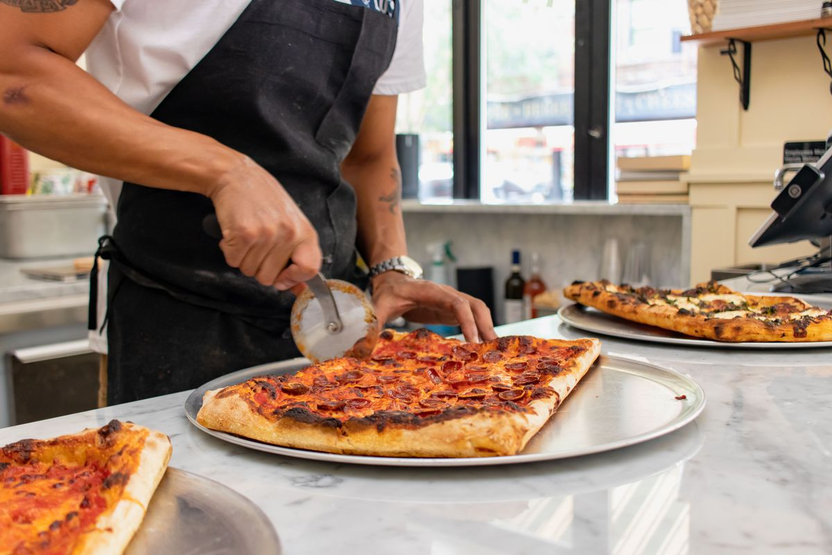Someone wearing an apron and a white shift uses a pizza cutter to divide a square pie