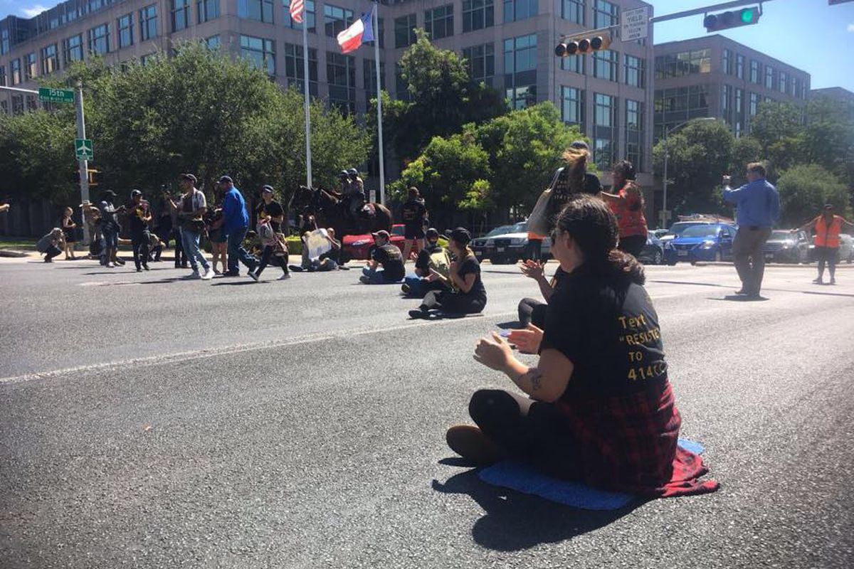 People sitting the middle of a street