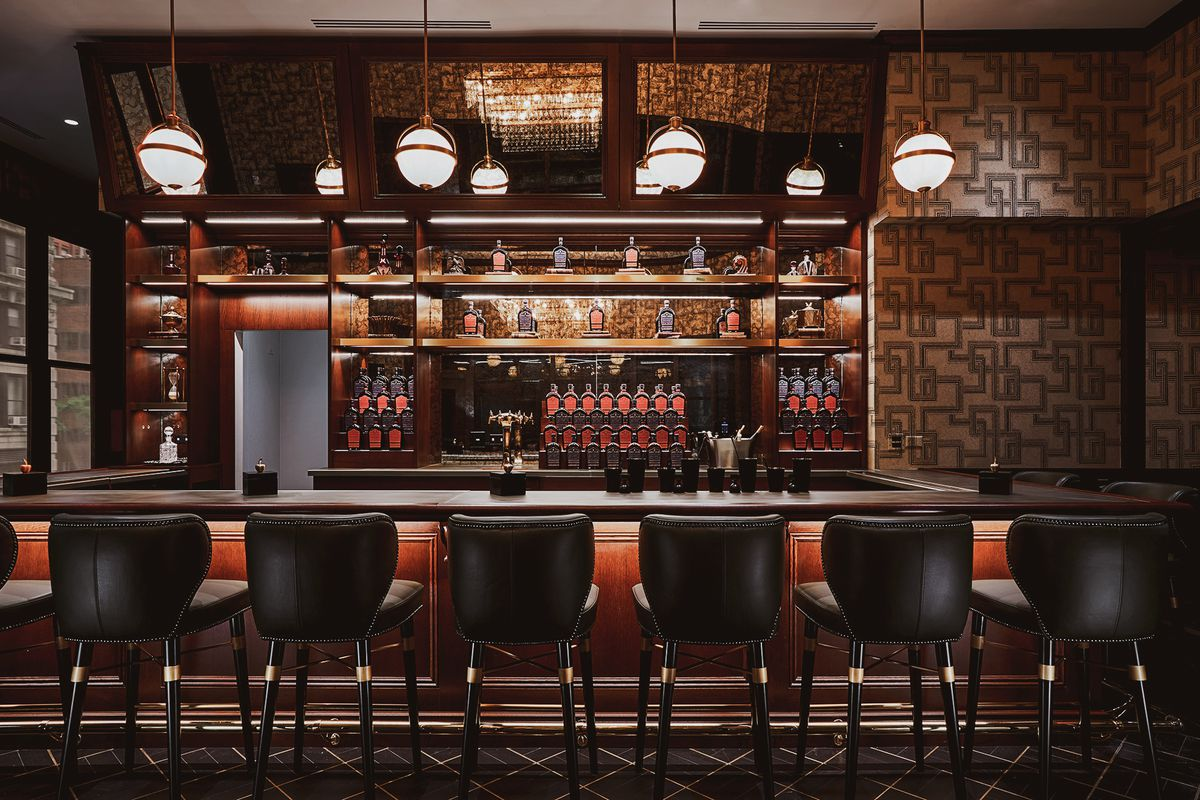 Dark-colored stools are lined up at a dimly lit bar, which advertises bottles of whiskey lined up on a back counter