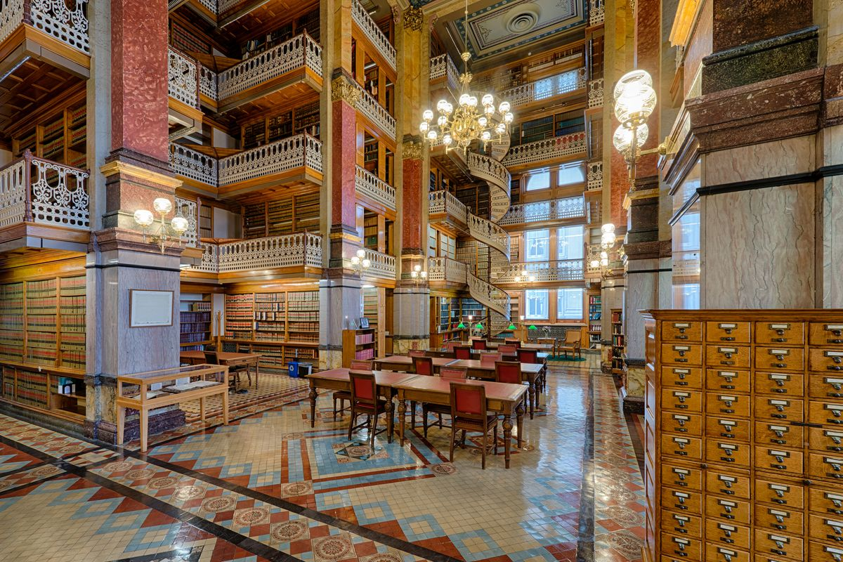 The interior of the State Library in the Capitol Building in Iowa. The ceiling has patterned tiles. There are hanging chandeliers. There are bookshelves full of books on multiple levels.