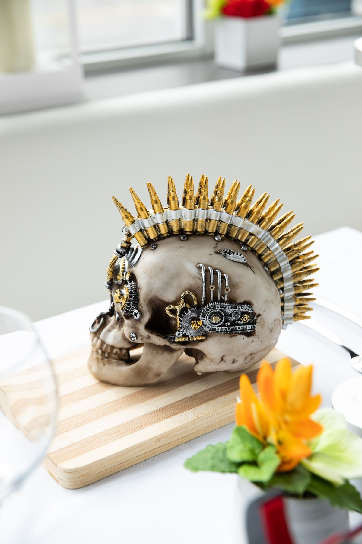 A silver skull on a cutting board with a bullet casing mohawk