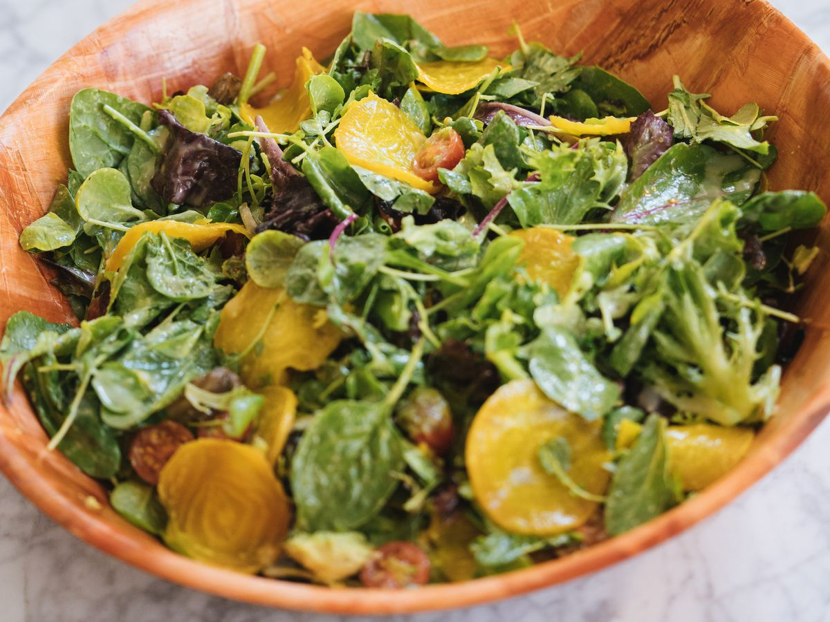 A salad with yellow beets in a brown bowl with a sign behind it that says Sa Pa Salad.