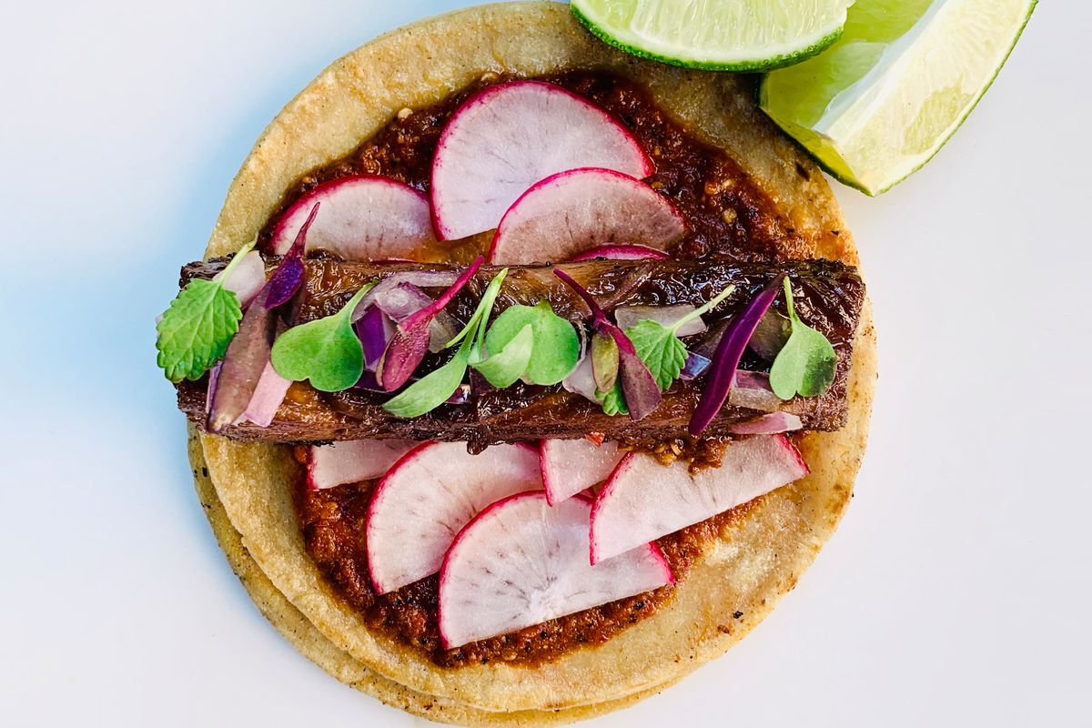 A tortilla filled with sauce, meat, and radish slices, sprinkled with micro cilantro and two lime wedges off to the side