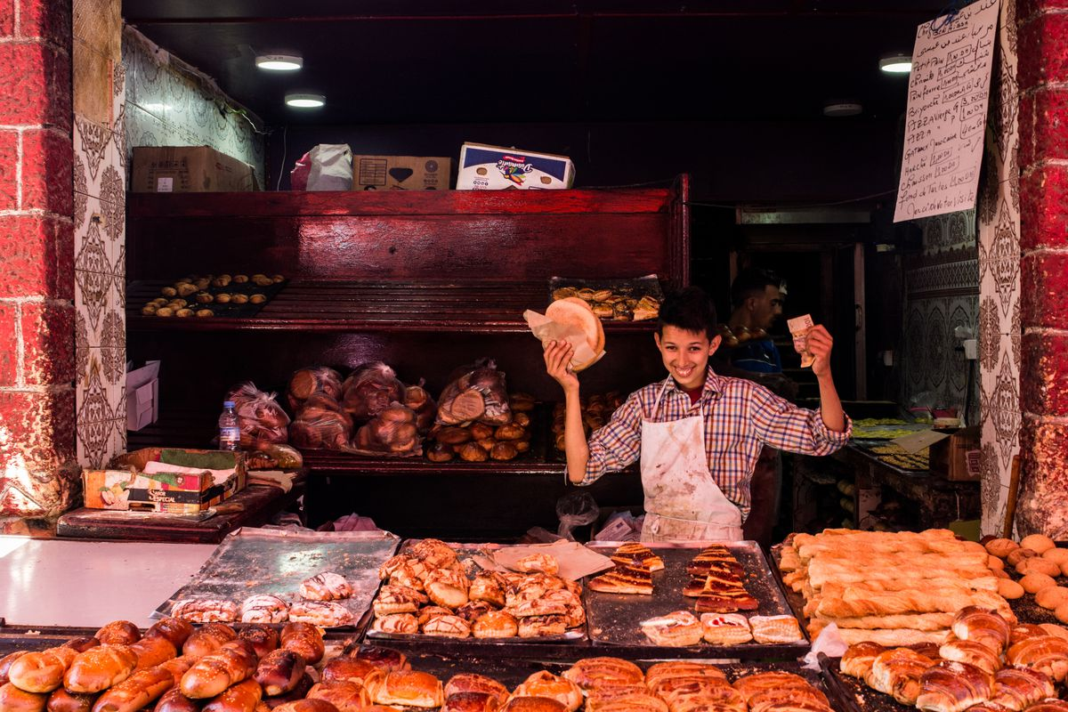 A worker holds a loaf of bread up at a market in Casablanca.