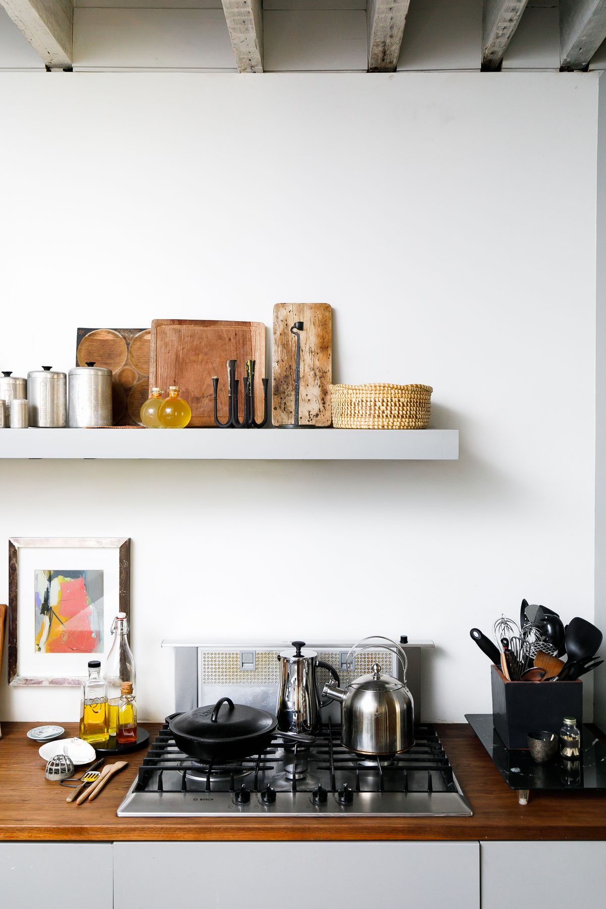 A stovetop with a kettle and a pan. Above the stovetop is a floating bookshelf with a collection of cutting boards and containers..