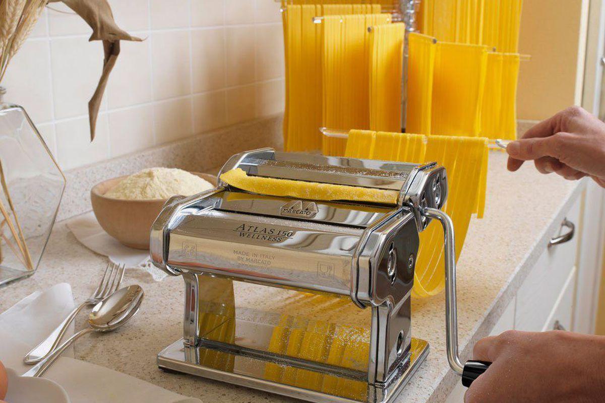 A person using a hand-crank pasta-maker