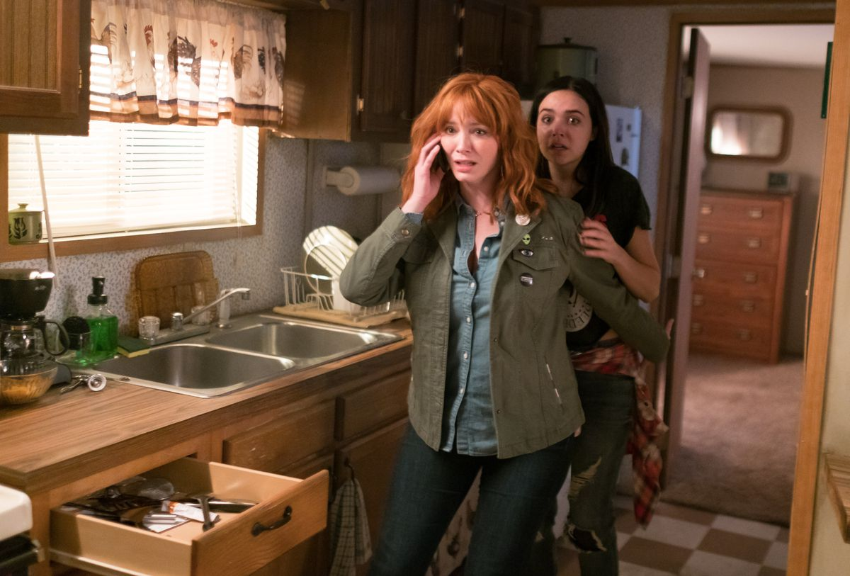 """Cindy (Christina Hendricks) and her daughter Kinsey (Bailee Madison) attempt to call for help while being terrorized by a masked stranger in """"The Strangers Prey at Night.""""   Brian Douglas / Aviron Pictures"""