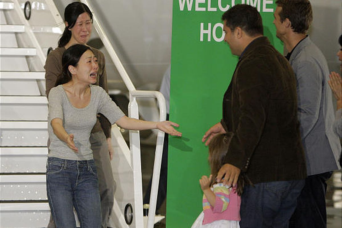 Euna Lee, left, and Laura Ling greet their families as they arrive in Burbank Wednesday after being freed from North Korea.