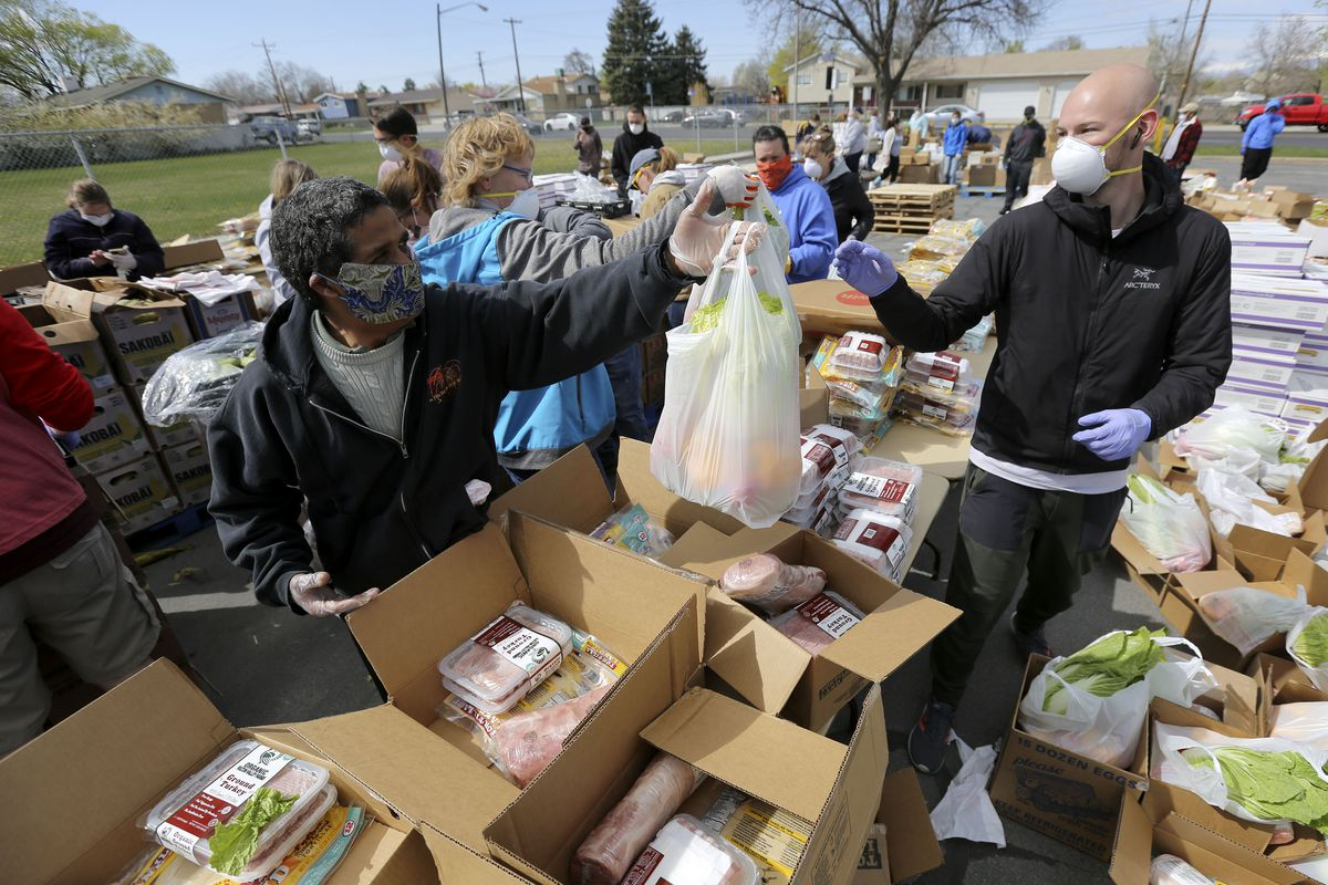 Jose Magallanes hands a bag of food to Chris Tibbitts as they prepare to hand out food from the Utah Food Bank in the parking lot of a chapel belonging to The Church of Jesus Christ of Latter-day Saints in Taylorsville on Monday, April 13, 2020. The Utah Food Bank estimates they provided food to around 400 families at this location.