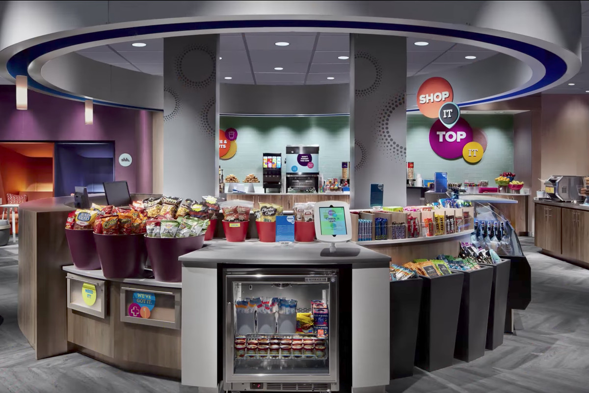 Rendering of a colorful cafeteria with circular booth with snacks and seating.