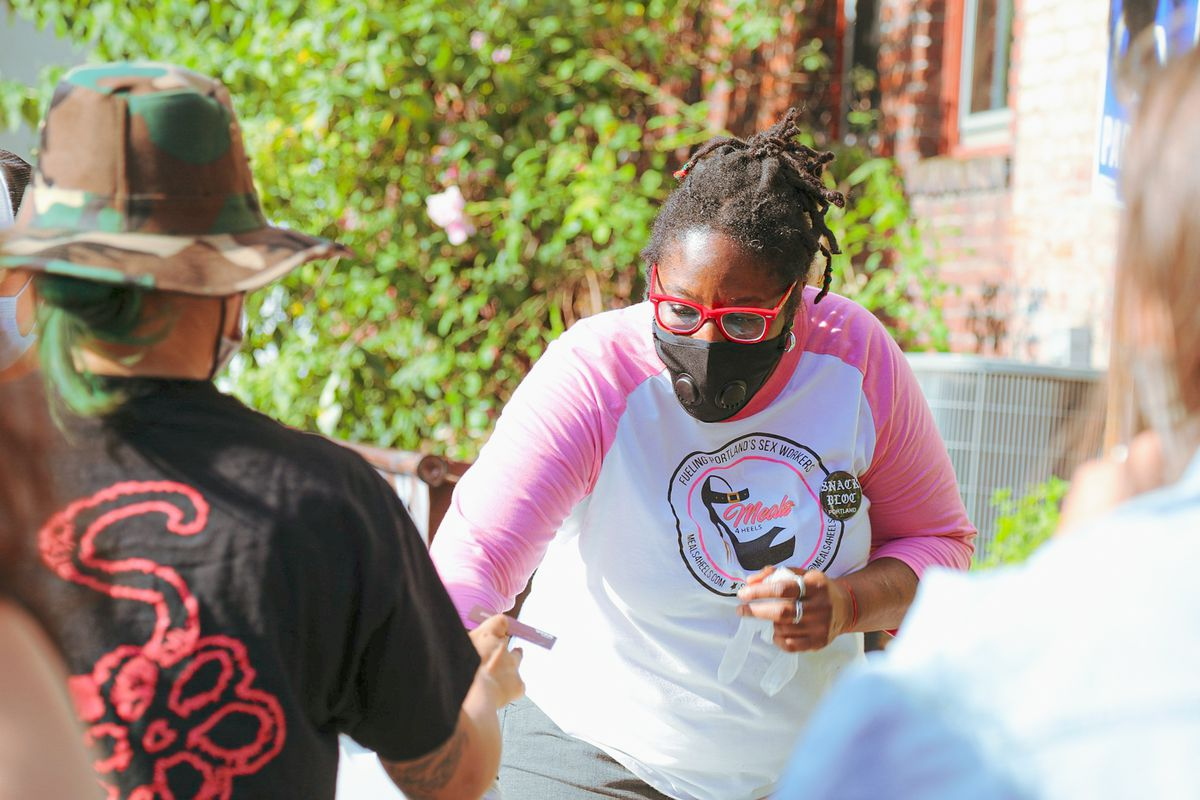 A woman with red glasses, a black face mask, and dreadlocks hands a bowl to a protester in a hat and a black shirt.