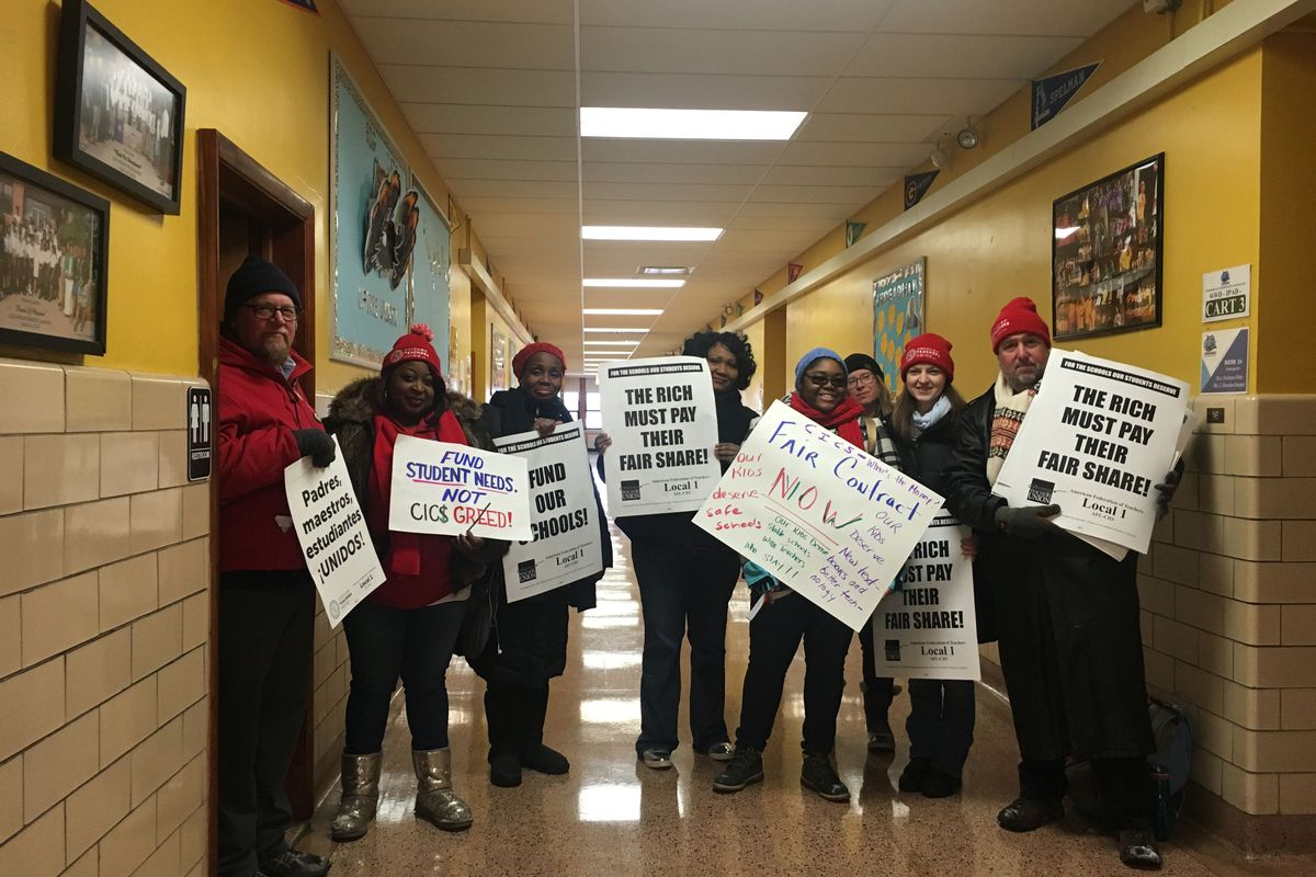Teachers and union members at CICS Wrightwood stand with protest signs.
