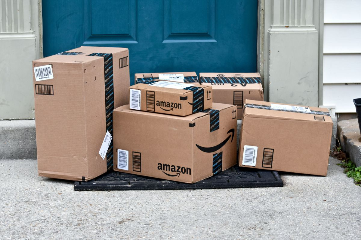 Amazon shipping boxes piled on a doorstep.