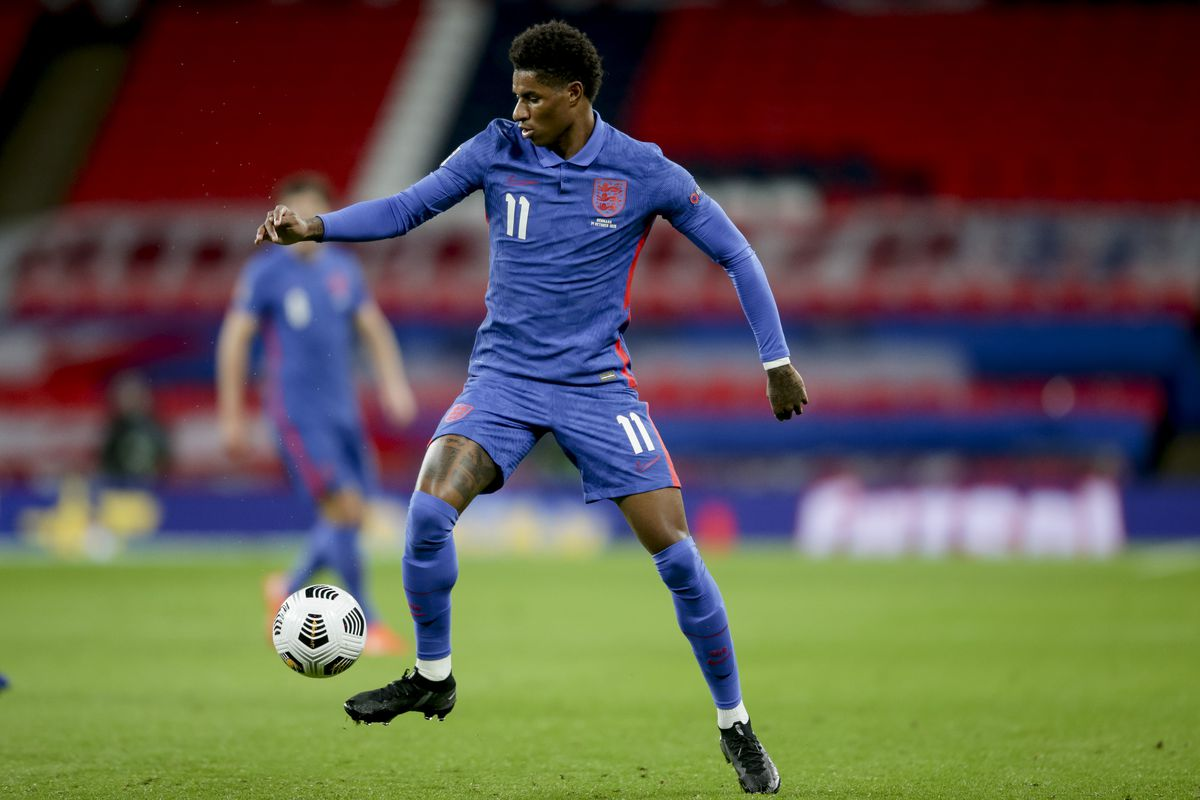 Footballer Marcus Rashford dressed in England's blue football kit, controlling the ball with his right foot during a match against Denmark