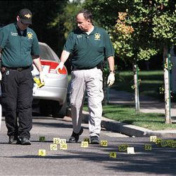 Visalia Police detectives point to an area where a suspect was shot after Bishop Clay Sannar of the Church of Jesus Christ of Latter-day Saints was shot and killed Sunday, Aug. 29, 2010 in Visalia, Calif.