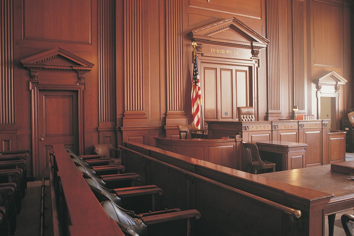 A courtroom sits empty, with deep brown walls and an American flag standing behind the judge's bench.