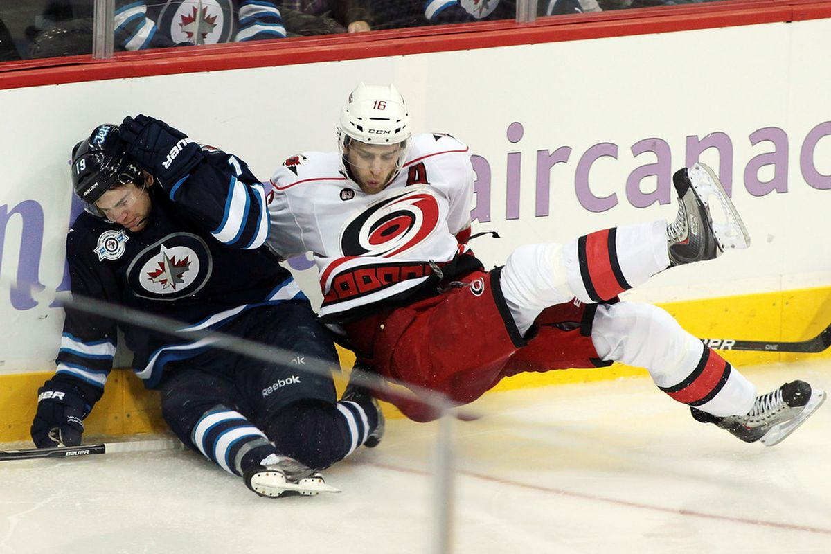 Both of tonight's teams are eager to get back in the playoff hunt. Jim Slater of the Winnipeg Jets slumps against the boards after colliding with Brandon Sutter of the Carolina Hurricanes at the MTS Centre on October 22, 2011 in Winnipeg.