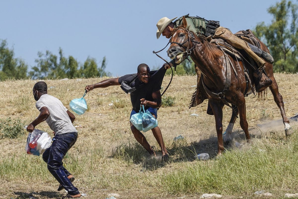 A white man on horseback grabs the shirt of a black man on foot.