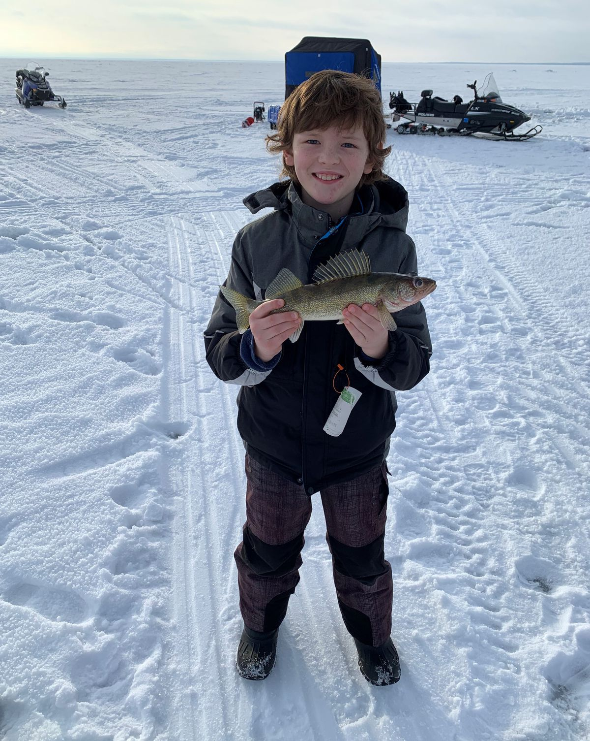Iowan Liam with his first walleye, caught from Mille Lacs. Photo provided by McQuoids Inn