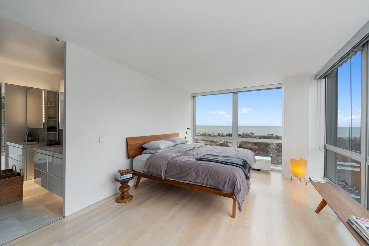 A corner bedroom with a contemporary wood framed bed and floor windows overlooking a park and large body of water.