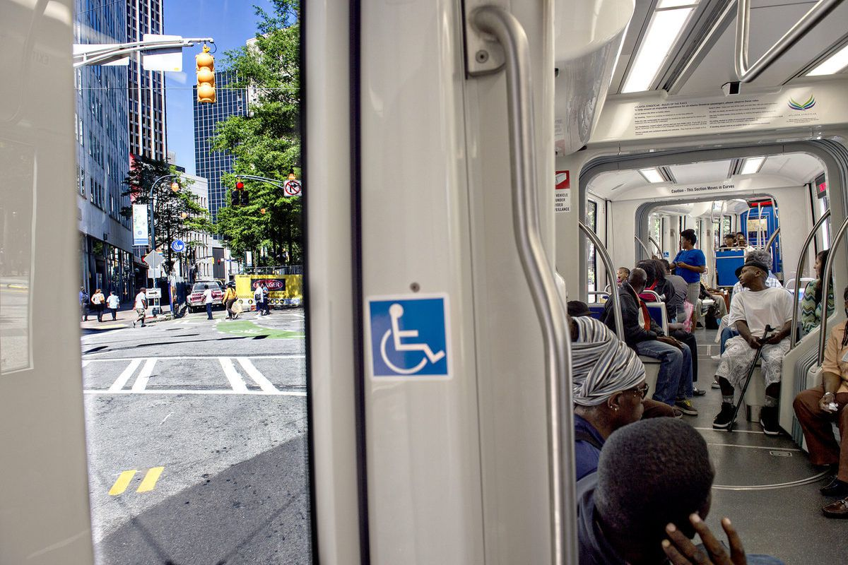 [An Atlanta Streetcar filled with passengers makes the turn towards the Hurt Park stop in downtown. Photos: Jonathan Phillips, Curbed Atlanta]