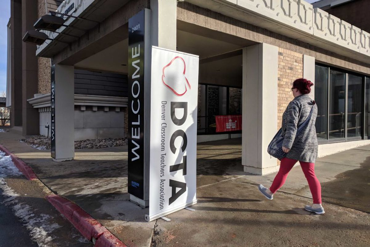 """A woman wearing a coat walks into a building. The building has a banner on it that says """"DCTA,"""" which stands for Denver Classroom Teachers Association."""