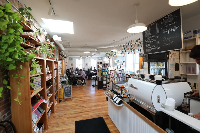 A narrow cafe with plants, wooden bookshelves, and a small espresso bar with a bright white espresso machine.