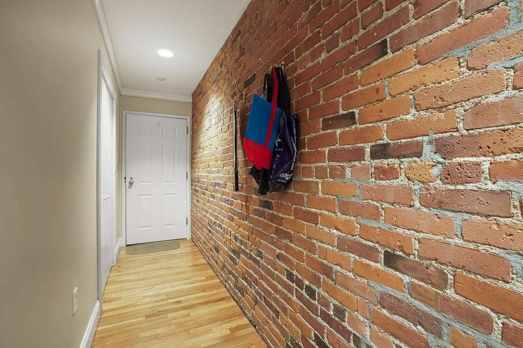 A long, narrow hallways leading from a front door, and one side is brick, and that side has a hook with a book bag on it.