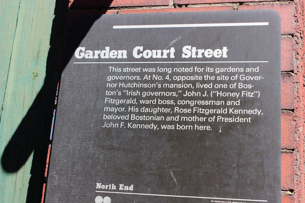 A placard on a brick building explaining the significance of the building.