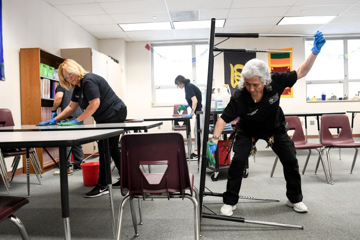 Gloved workers wipe tables and panels in a classroom.