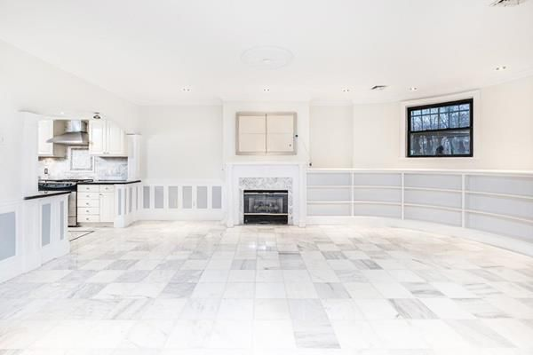 An empty and expansive living room next to a kitchen with a fireplace at the end.