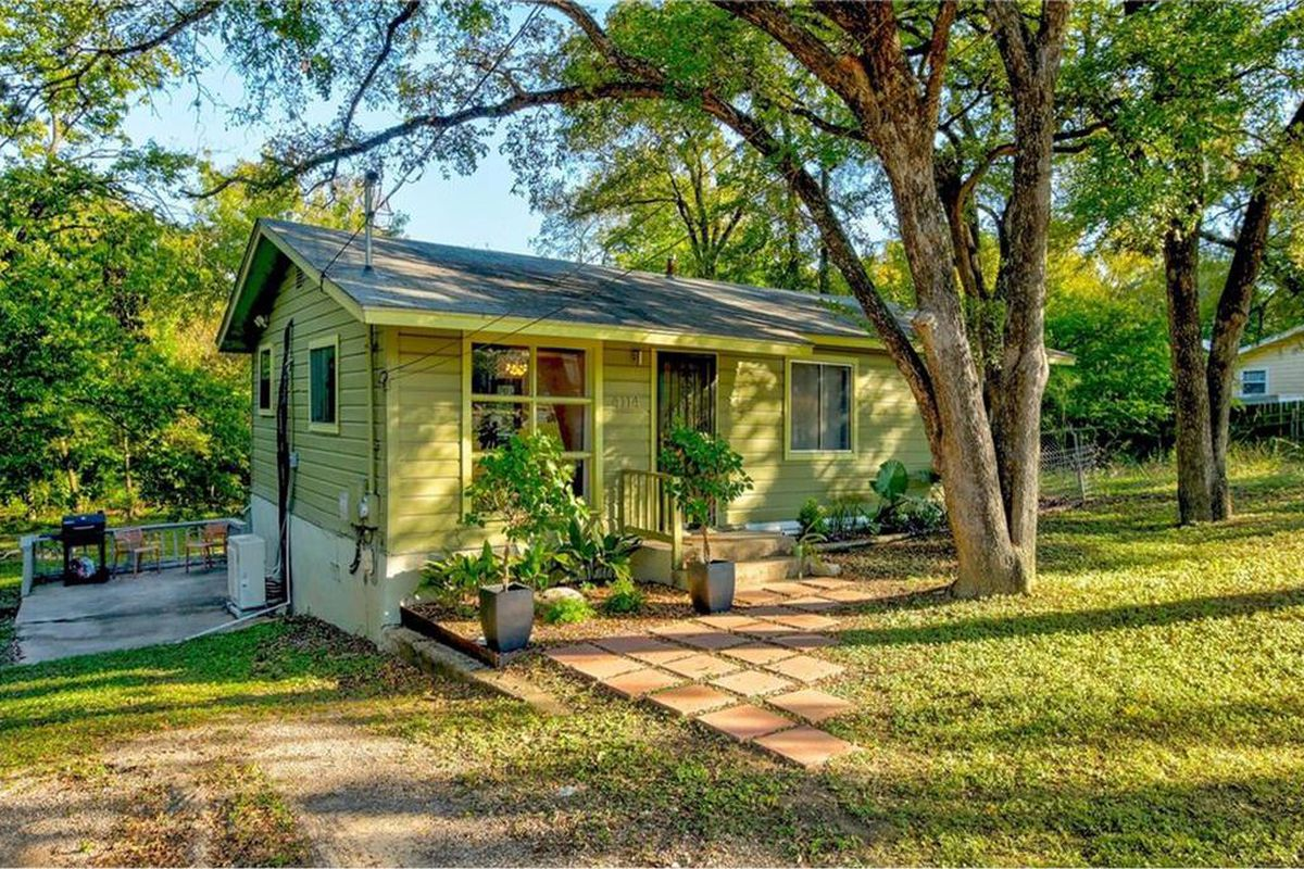 Small green frame home with large yard and trees