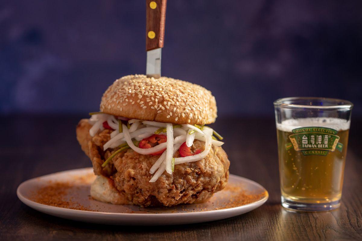 A knife stands upright like a toothpick inside 886's oversized fried chicken sandwich