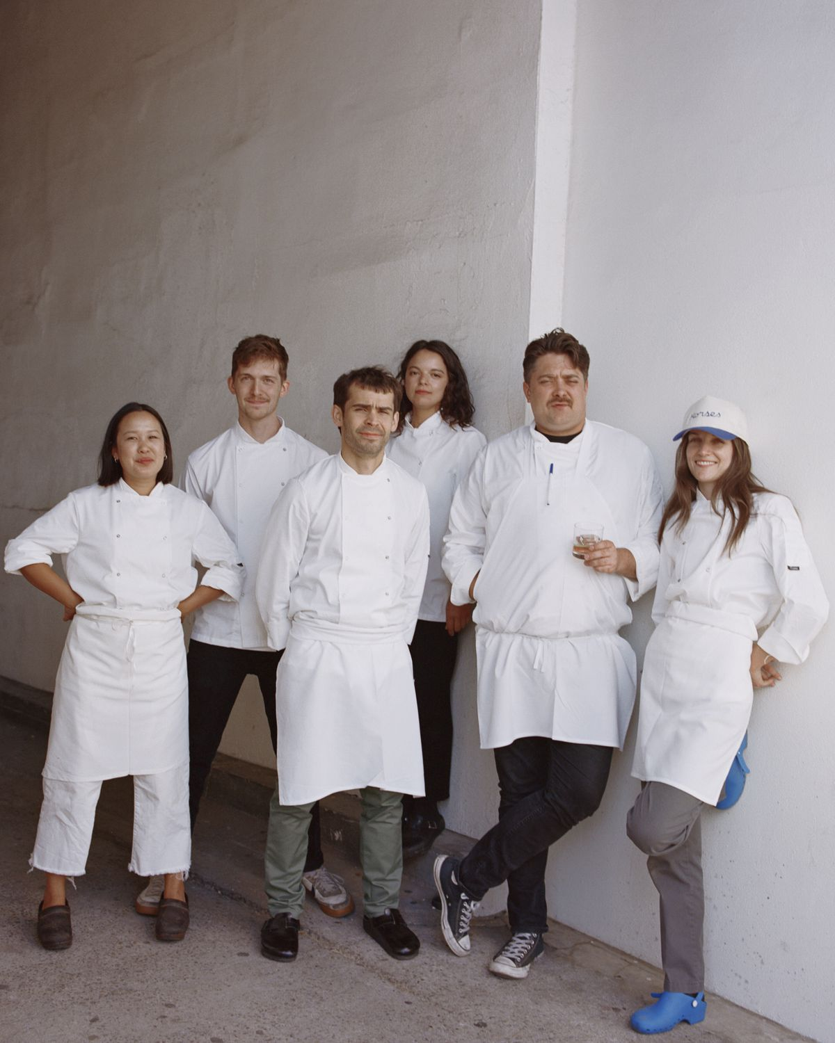 A group of white coat chefs and cooks in an alleyway behind a restaurant.