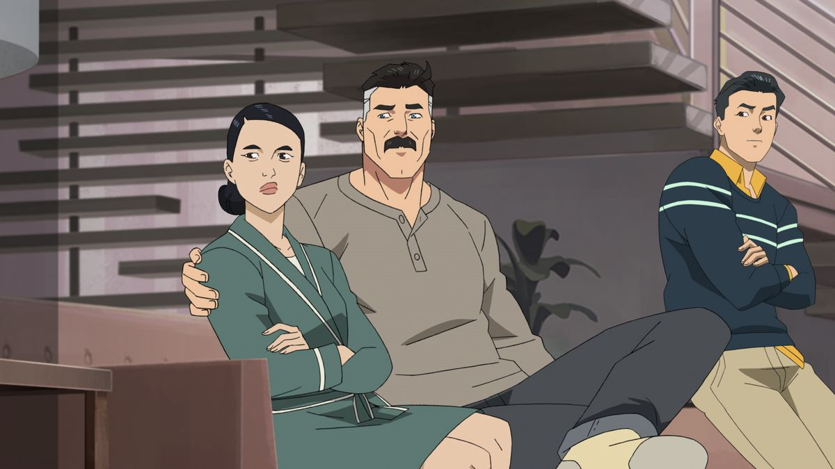 Nolan Grayson sits with his arm around Debbie on the couch, as Mark perches on the couch arm with his arms folded in Amazon's Invincible