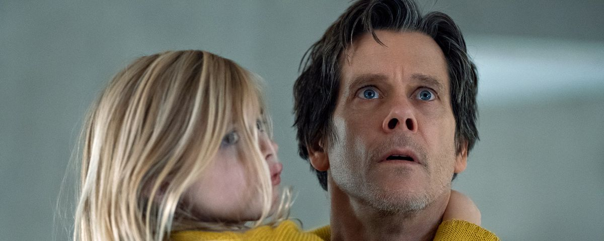Kevin Bacon's character in You Should Have Left looks fearful while holding up his 6-year-old daughter Ella, played by Avery Essex.