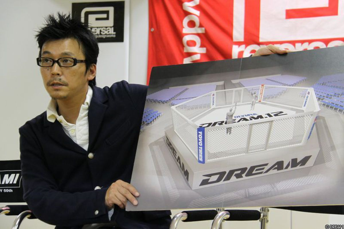 """Event producer Keiichi Sasahara holds up a simulation of DREAM.12's white cage at a press conference in Tokyo on Tuesday. Photo via <a href=""""http://www.dreamofficial.com/free/news/detail.php?id=1254205104"""" target=""""new"""">DREAM Official</a>."""