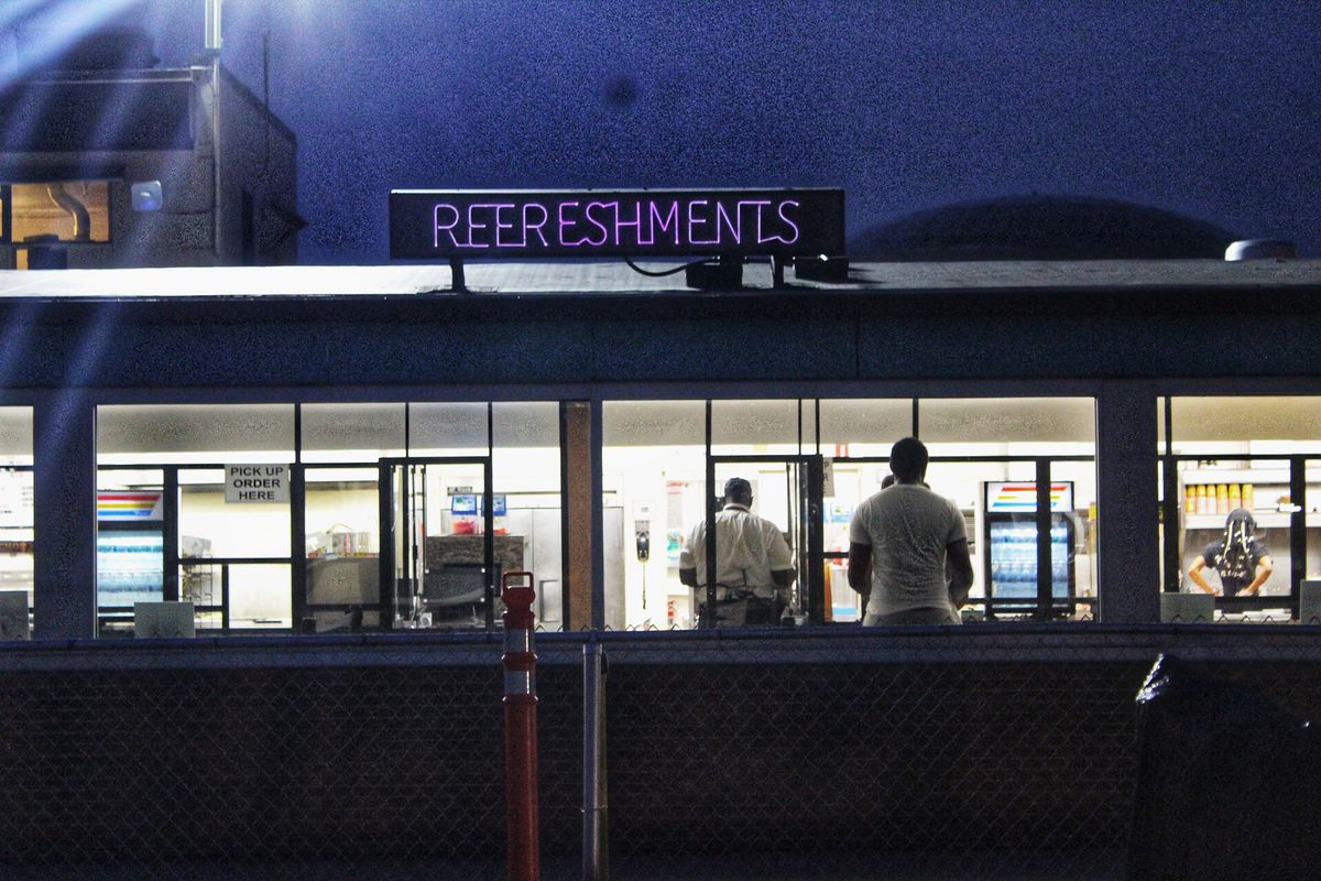 """A neon sign reading """"Refreshments"""" sits atop a food vending section at a drive-in movie theater."""