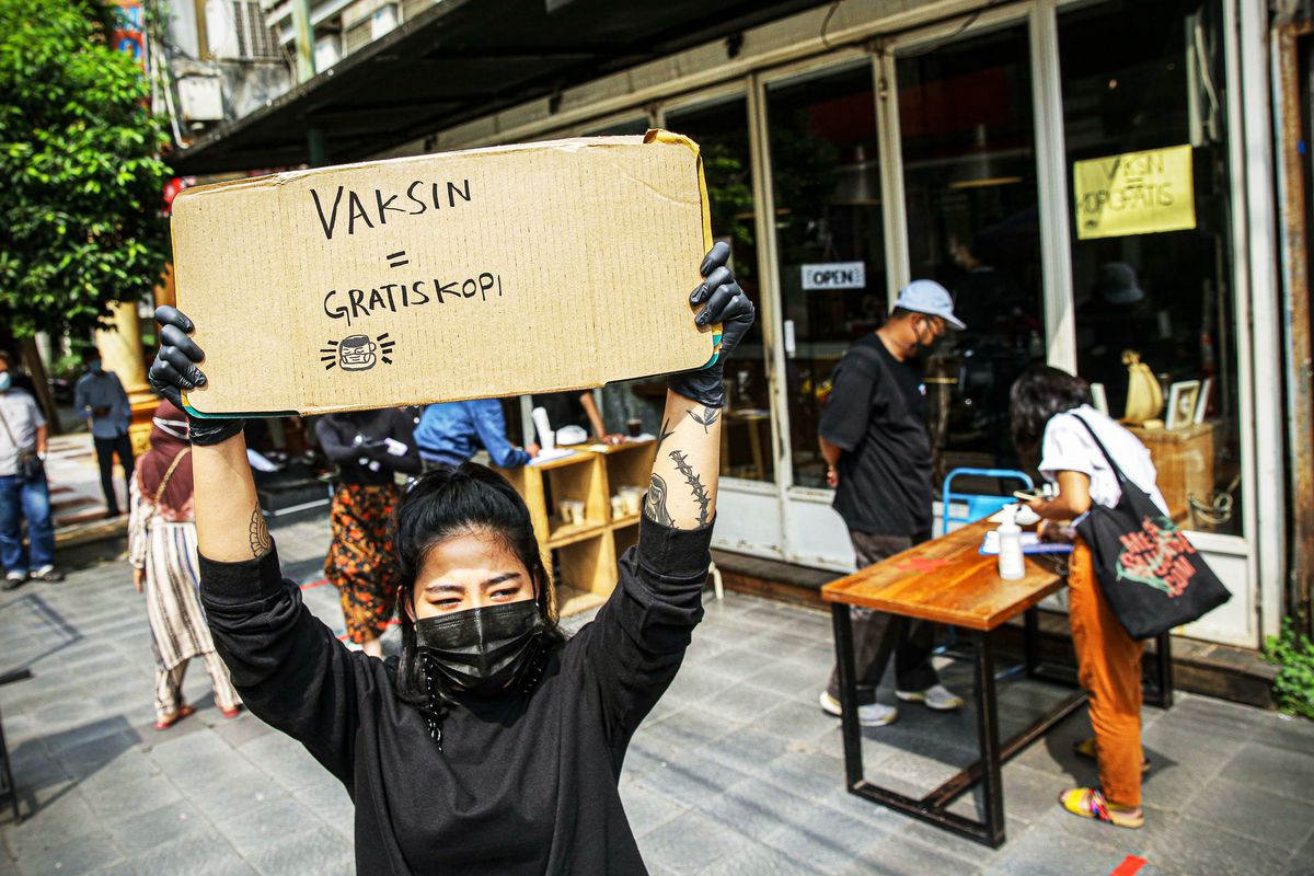 """A person outside a coffeeshop in Jakarta holds up a hand-lettered sign that reads """"Vaksin = gratiskopi,"""" or """"Vaccine equals free coffee."""""""