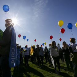 Jennifer Lowery, right, listens to a performer before the speeches start during the March to End Child Abuse, organized by Protect Every Child, on the lawn of the state Capitol in Salt Lake City on Saturday, Oct. 5, 2019. The marchers carried red, yellow and blue balloons which match the logo of Protect Every Child.