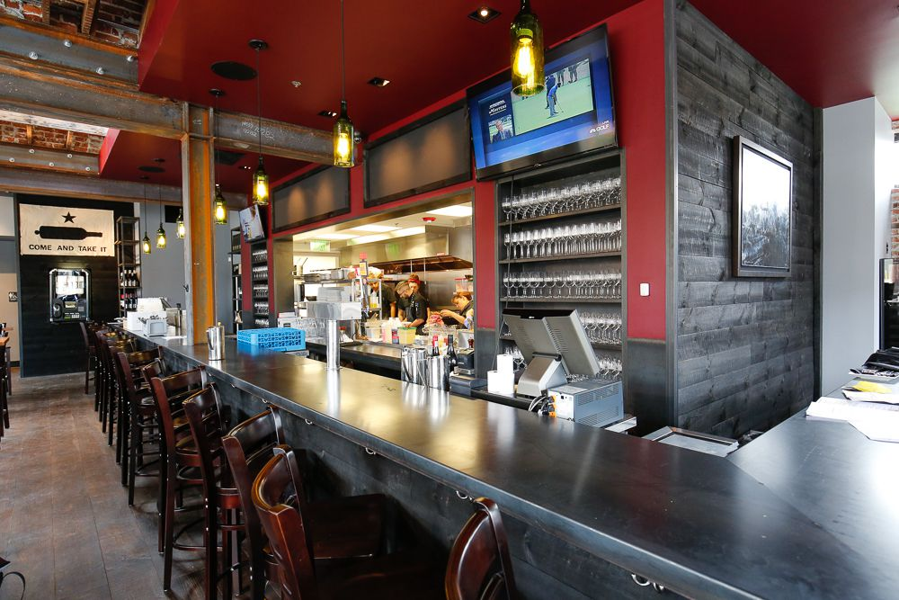 A photo of the bar at Max's Wine Dive with a TV screen and shelves containing wine glasses visible behind it